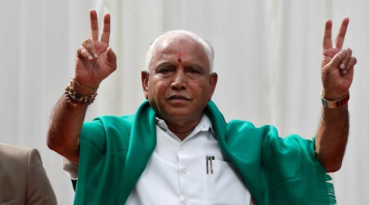 BJP leader B. S. Yeddyurappa flashes the victory sign after taking oath as Chief Minister of the southern state of Karnataka inside the governor's house in Bengaluru